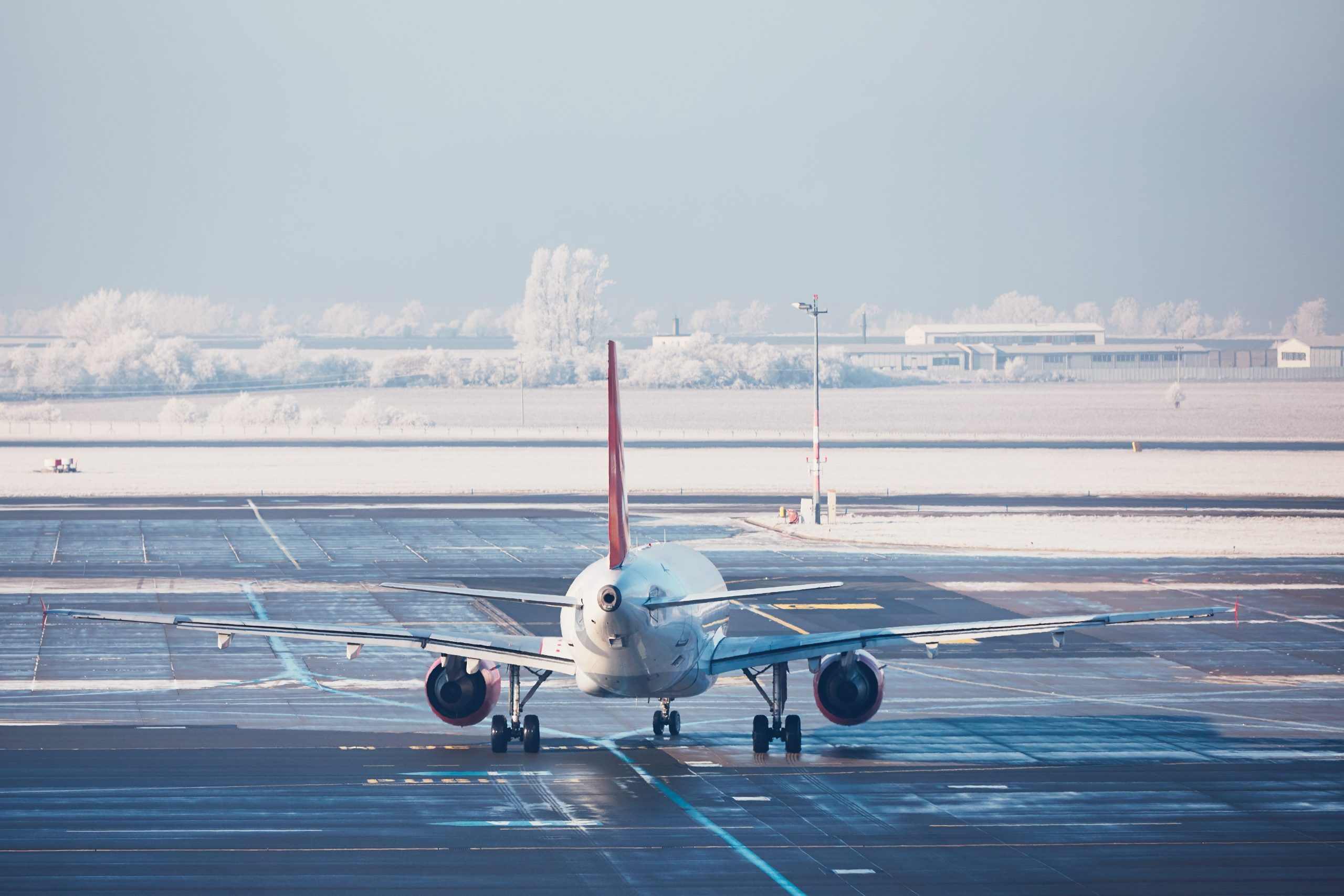 Airport in winter. Airplane is taxiing to the runway for take off.